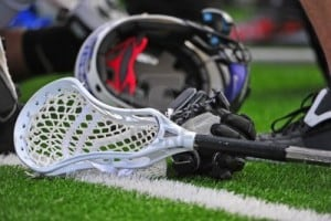9227795-high-school-boys-varsity-lacrosse-stick-head-laying-on-a-turf-field-with-a-glove-and-helmet-in-the-b