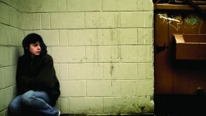 Young-boy-in-black-hoodie-next-to-dumpster-849x480