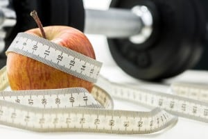 Closeup of apple wrapped with measuring tape and weights in background. Conceptual of fitness and dieting.