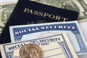 Close up photograph of social security cards, passport and dollar coin with paper currency, selective focus.