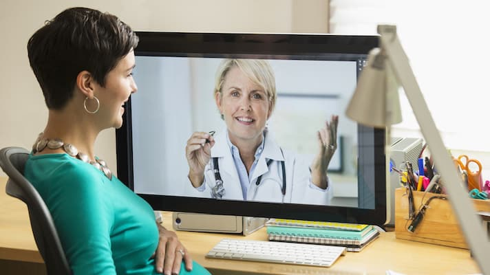 Pregnant mixed race businesswoman video chatting with doctor